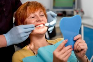 woman looking in mirror dental implant