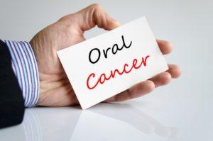 left hand holding oral cancer sign
